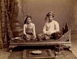 [Burmese couple of the upper class seated on a wooden couch.]
